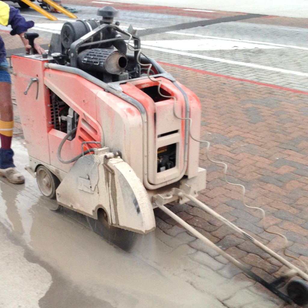 Cutting concrete edge in prep for replacing pavers